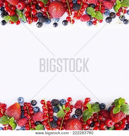 Black-blue and red fruits. Ripe red currants, strawberries, raspberries, blackberries, blueberries and blackcurrants on white background. Berries at border of image with copy space for text. Background berries. Various fresh summer berries isolated on a w