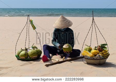 Beach Fruit Salesman Resting on the Sand in Vietnam. He is selling Coconuts, Bananas and other exotic fruits