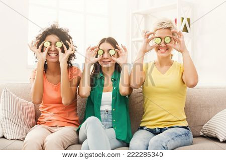 Three beautiful girls in colourful clothes having fun, covering eyes with cucumber pieces