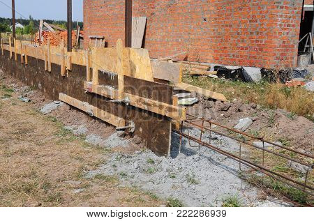 Building concrete foundation with slabs and iron bar for new fence. Fencing.