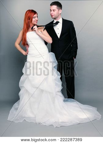 Wedding day. Portrait of happy married couple red haired bride and groom in full length. Woman pulling on mans tie, studio shot on gray background