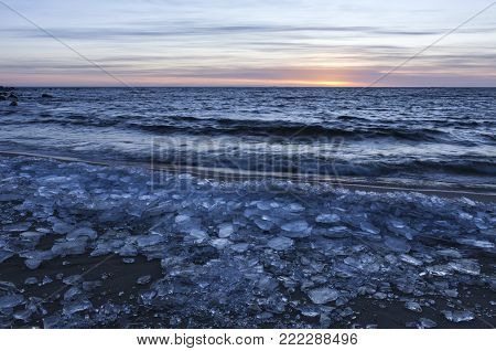 Sunset by the Baltic Sea on the Winter Solstice day 2017. Blocks of ice on the sandy shore.