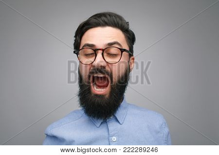 Handsome bearded man yawning with eyes closed on gray background.
