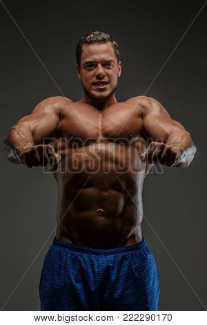 Muscular guy showing his muscles. Isolated on grey