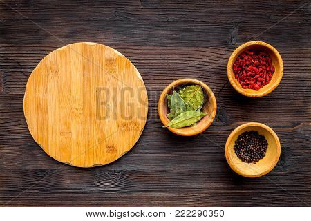 Make menu or write recipe. Mock up for menu or recipe. Wooden cutting board near ingredients in bowls bay leaf, black repper and godji on dark wooden background top view.