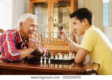 Happy little kid playing chess with senior man at home. Family relationship with grandfather and grandson. Grandpa and male grandchild playing board game
