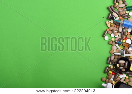 Set Of Colorful Pills Scattered On Green Background