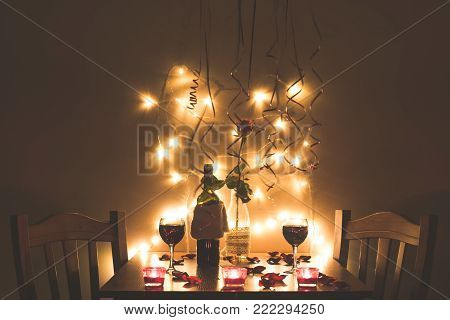 Home style restaurant interior at night. Table close up with glass of wine, lights and roses