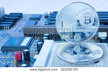 On a printed circuit motherboard are silver coins of a digital crypto  currency - bitcoin and one cent in blue.