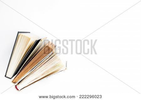 Reading and self-development. Old books on white background top view copy space.