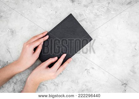 Reading and self-development. Hands hold old book on grey background top view.