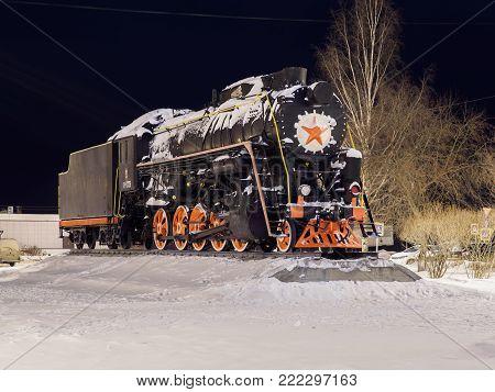 night view of old soviet steam locomotive on pedestal in kotlas city