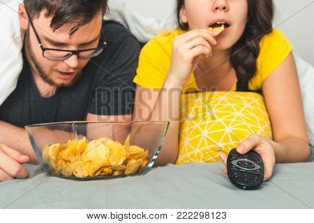 couple watch movie together in bed and eat snacks from the bowl