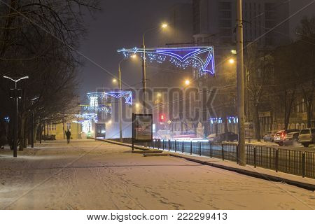15 January , 2018 . City Dnipro. Ukraine. Winter in the city. Night snowbound city.  Street  covered with snow, illuminated by lights and illumination.