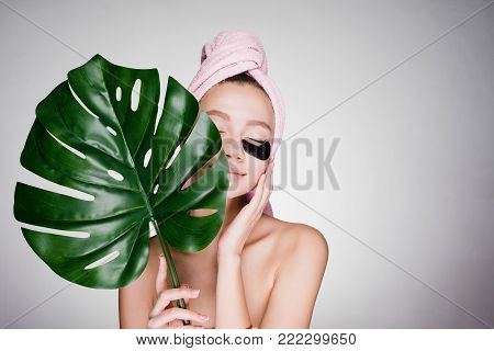 cute young girl with a pink towel on her head enjoying the spa, under the eyes of black patches, her eyes are closed