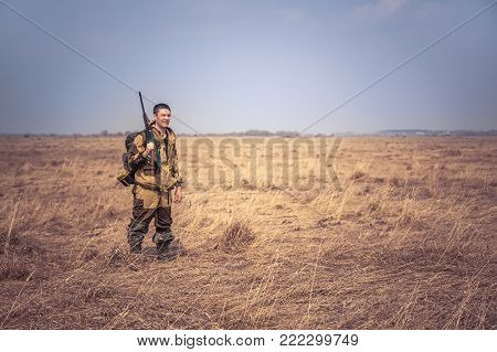 Hunter man with shotgun and hunting equipment  standing in dry rural field with dry grass and clear sky during spring hunting season