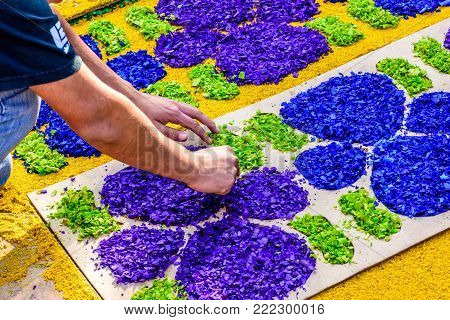 Antigua, Guatemala -  April 2, 2017: Decorating  dyed sawdust Lent procession carpet in town with most famous Holy Week celebrations in Latin America