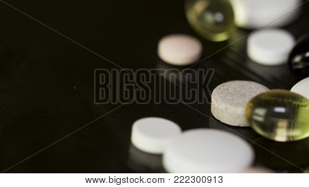 A Lot Of Tablets On The Black Background. Colorful Pills And Needle On Black Background, Low Contras