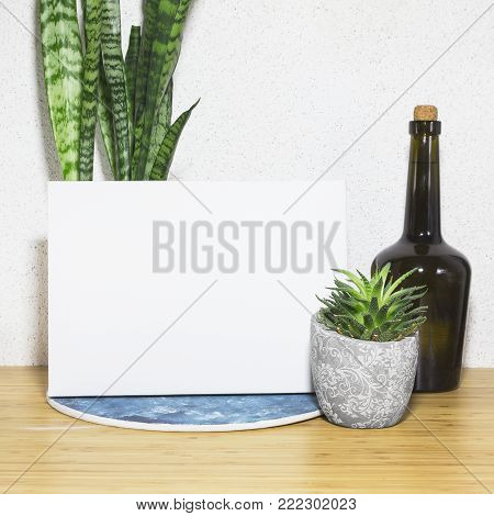 Mockup poster in interior. Blank canvas, decorative bottle and houseplant.
