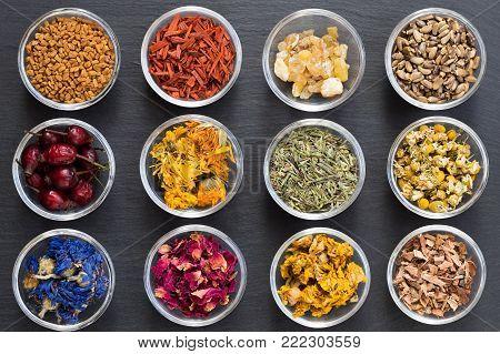 Selection of herbs on dark background - fenugreek, sandalwood, frankincense resin, milk thistle, dried rose hips, calendula, horsetail, chamomile, cornflower, rose petals, mullein, oak bark