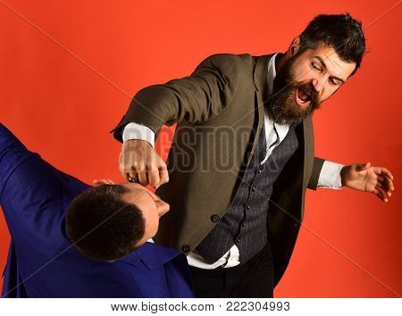 Businessman Wearing Smart Suit Punches Or Hits Colleague.