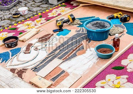 Antigua, Guatemala -  April 13, 2017: Decorating  dyed sawdust Holy Thursday procession carpet in town with most famous Holy Week celebrations in Latin America