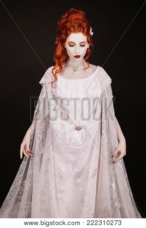 Vampire clothes for Halloween. Girl dress gothic outfit for halloween. Interesting gothic outfit for Halloween. Celebrate Halloween. Prepare vampire look on Halloween. A woman is a vampire with pale skin and red hair in a black dress and a necklace