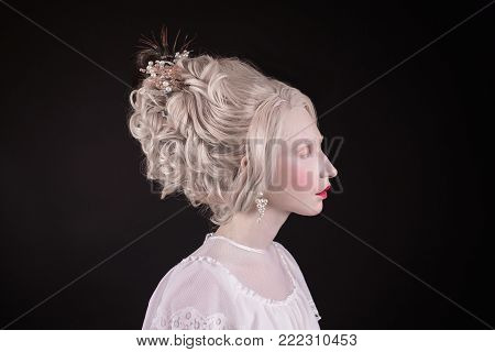 Girl with beautiful hairstyle. Blonde in retro dress with chic hairstyle. A young model with a luxurious hairstyle. Girl with natural make-up and high hairstyle. Original hairstyle