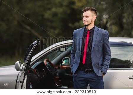 Successful stylish businessman in a dark stylish business suit with a red tie against the background of a car. Stylish man. Fashionable stylish watch on hand. Stylish young man in red tie