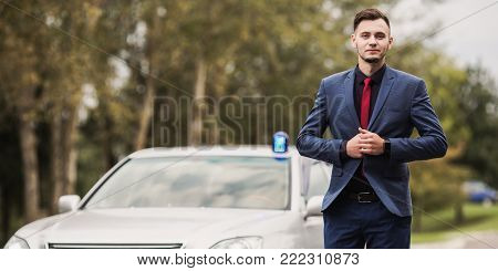 A successful rich businessman in a dark business suit with a red tie is sit down in the car. Stylish rich man. Rich man in a classic suit. Become very rich