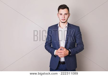 Interesting photo with people. Successful young business people with a business suit on gray background. Conceptual photography with people. An unusual image of people. Young people in the picture. Stylish man. Director of the firm.