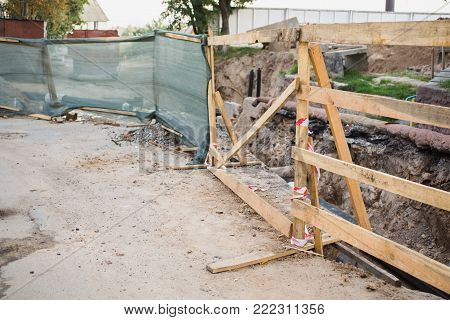Barrier for security. Wooden barrier on the road. The barrier blocks the pit. Barrier in the yard of the house. Barrier from a dry tree