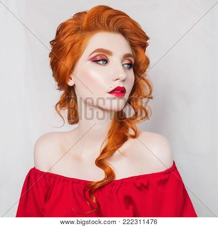Red-haired lady girl with pale skin in a red retro dress. Lady with natural fur on her shoulders against dark background. Vintage lady. Young lady. Lady in long tight dress