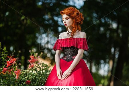 Interesting photo with people. Conceptual photography with people. An unusual image of people. Young people in the picture. Beautiful red-haired girl in a red dress and in black corset on a green background. A woman with red hair in a summer forest