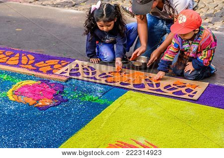 Antigua, Guatemala -  April 14, 2017: Decorating dyed sawdust Good Friday procession carpet in town with most famous Holy Week celebrations in Latin America
