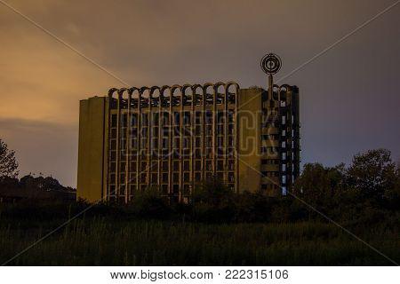 Ruined abandoned multi-story building at night. Abandoned sanatorium in Eshera, Abkhazia, Georgia.