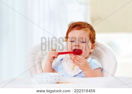 cute little infant baby boy learn to hold the spoon and eat by himself