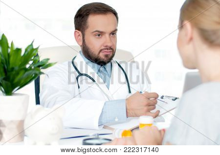 Doctor and patient. Doctor is writing prescription to patient