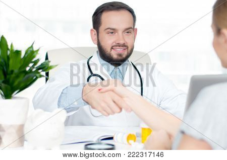 Doctor and patient. Smiling doctor shaking hands with a female patient in the office