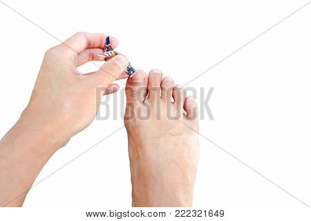 Hand Holding Nail Clippers. And Cut The Nail On The Foot.