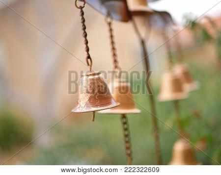 Golden Wind Chime Bells with Plants in Garden