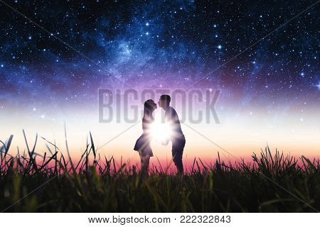couple in love in the field against the sunset and stars