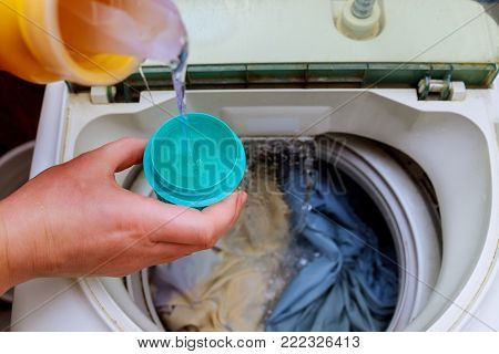 Woman hand pouring washing powder into the washing machine washing powder into the washing machine