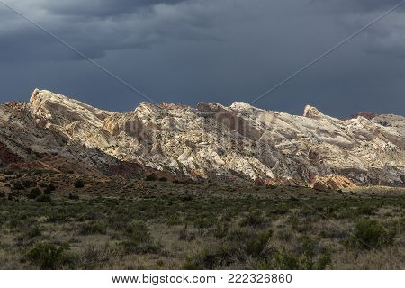 Waterpocket Fold in Capitol Reef National Park in Utah USA shining in the sun of an otherwise stormy day.