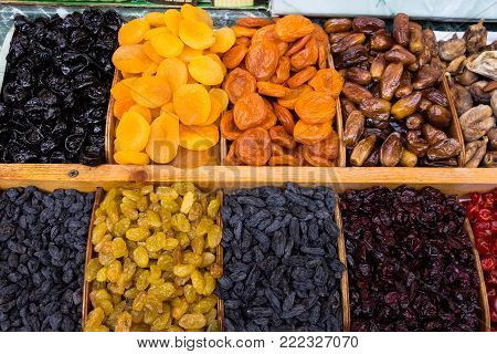 dry fruit mix on a pile on a food market, coloful dry fruits, dried fruits, different types of dry fruits, Assortment of dried fruits closeup background in square cells. Decorative pattern of dry exotic fruit. Top view.