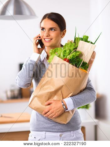 Young housewife sort purchases after shopping Young housewife sort purchases after shopping