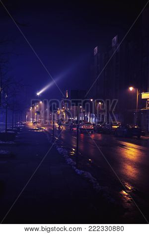 Small Balkan town in winter, at night, with fog and some passerby.