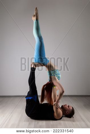 guy and young woman doing strength exercises in yoga assanes. Acroyoga concept.
