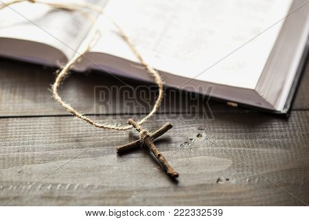 Christian wooden cross next the open Holy Bible. The way to the God through prayer. Cross next the pages of the book.