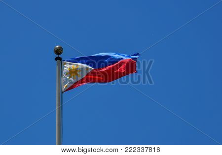 Flag of the Philippines waving in the blue sky.